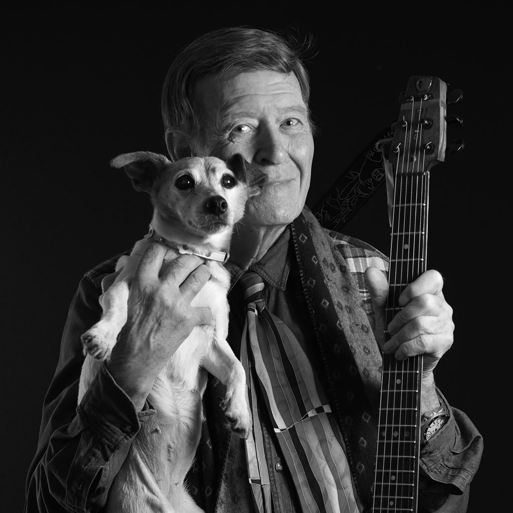 man holding a jack russel dog in a studio photo