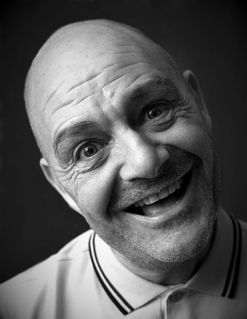 B&W photo of a man with a shaved head, smiling.