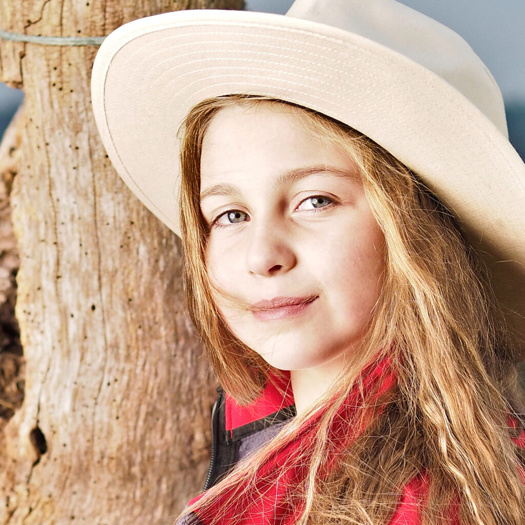a photo of a pretty young girl with a straw hat