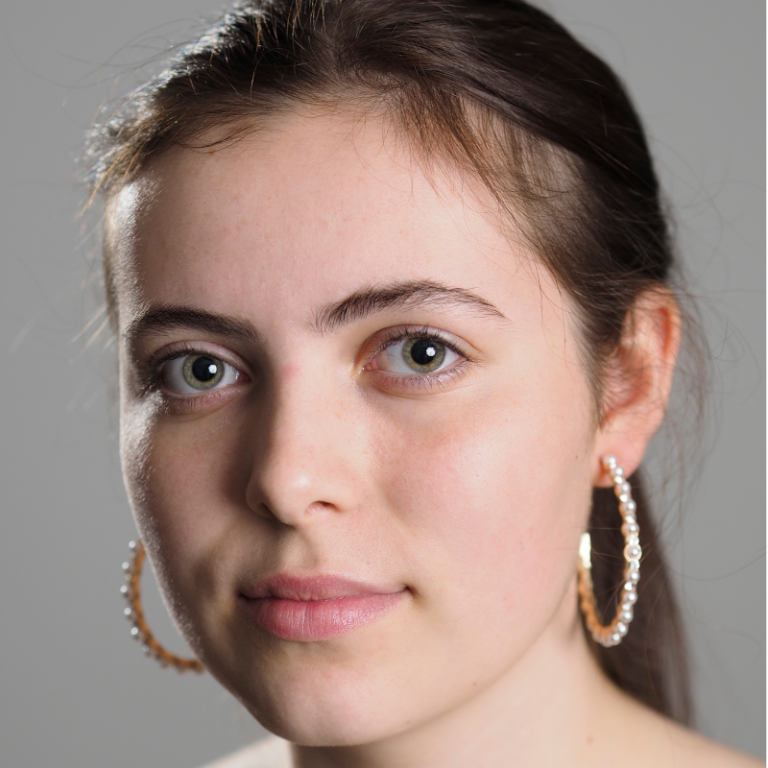 a studio portrait of a young woman wearing earings